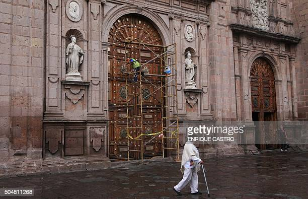 Workers clean the entrance of the cathedral in Morelia Michoacan state Mexico on January 13 2016 Pope Francis will offer a mass in Morelia during his...