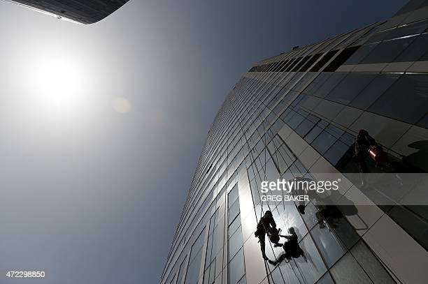 Workers clean the exterior of a shopping mall in Beijing on May 6 2015 China on May 1 announced measures aimed at promoting innovation and job...