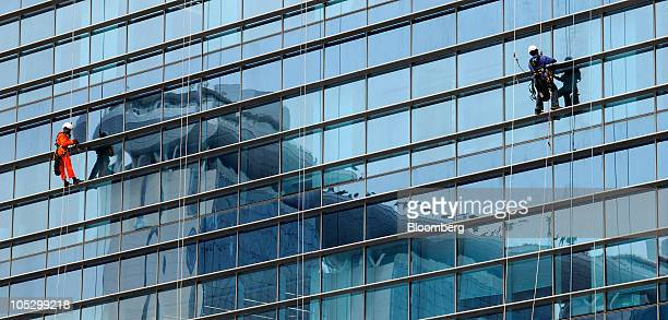 Workers clean the glass facade of an office tower in the new Marina Bay Financial Centre in Singapore on Wednesday Oct 13 2010 Singapore's economy...