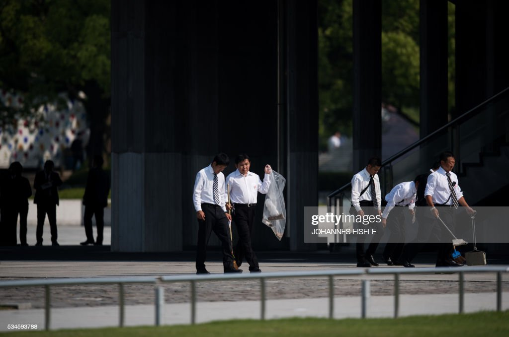 Workers clean the Hiroshima Peace Memorial park in Hiroshima on May 27, 2017. US President Barack Obama was to make history later on May 27 when he travels to Hiroshima -- becoming the first sitting US leader to visit the site that ushered in the age of nuclear conflict. / AFP / JOHANNES