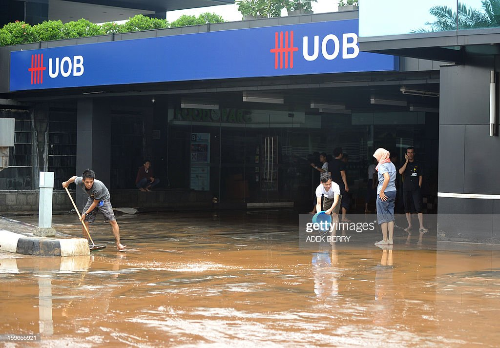 Workers clean the lobby of the UOB building where two people were trapped by floodwaters in the basement in Jakarta on January 18, 2013. Floods in Indonesia's capital Jakarta have left at least 11 people dead and two missing, authorities said as murky brown waters submerged parts of the city's business district, causing chaos for a second day. AFP PHOTO / ADEK BERRY