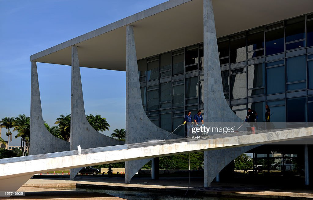 Workers clean the Planalto Palace ramp in Brasilia, on December 6, 2012, awaiting for the arrival of the coffin with the remains of Brazilian renown architect Oscar Niemeyer, who died on the eve in his hometown Rio de Janeiro. Niemeyer, the Brazilian icon who revolutionized modern architecture and designed much of the country's futuristic capital Brasilia, died in Rio Wednesday at 104. The architect's body was to be flown to Brasilia Thursday for a funeral wake at the presidential palace, one of his major works. The body was then to return to Rio for another funeral wake followed by the burial, according to Rio Mayor Eduardo Paes. AFP PHOTO/PEDRO LADEIRA