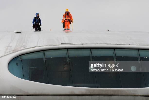 Workers clean the roof of the Media Centre as the England and Wales Cricket Board hold the launch of the domestic cricket season at Lord's Cricket...