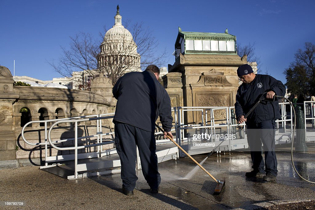 Workers clean the sidewalk in front of the Capitol building ahead of the presidential inauguration in Washington, D.C., U.S., on Sunday, Jan. 20, 2013. As he enters his second term U.S. President Barack Obama has shed the aura of a hopeful consensus builder determined to break partisan gridlock and adopted a more confrontational stance with Republicans. Photographer: Victor J. Blue/Bloomberg via Getty Images