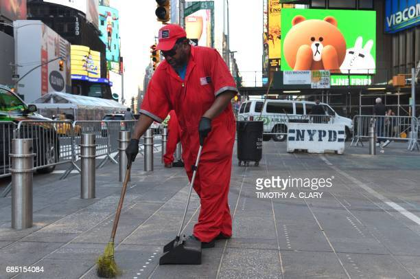 Workers clean the sidewalk in Times Square May 19 2017 the morning after Richard Rojas crashed his car into a a crowd of pedestrians in New York's...