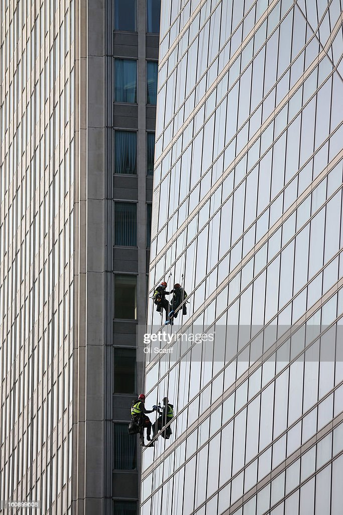 Workers clean the windows of an under-construction, mixed use office and retail building on Victoria Street on February 7, 2013 in London, England.