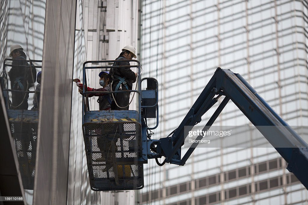 Workers clean the windows of CCB Tower, which houses the local operations of China Construction Bank Corp., in the central business district of Hong Kong, China, on Friday, Jan. 4, 2013. Hong Kong topped the ranks as the most expensive office market by total occupancy cost, according to a report by CBRE Research released on Jan. 7. Photographer: Jerome Favre/Bloomberg via Getty Images