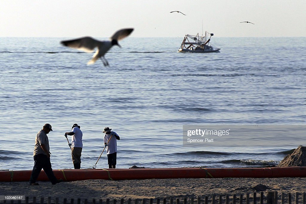 Workers clean up along a stretch of oil-contaminated beach June 14, 2010 in Grand Isle, Louisiana. The BP spill has been called the largest environmental disaster in American history. U.S. government scientists have estimated that the flow rate of oil gushing out of a ruptured Gulf of Mexico oil well may be as high 40,000 barrels per day. President Obama will make his fourth trip to the Gulf on Monday.