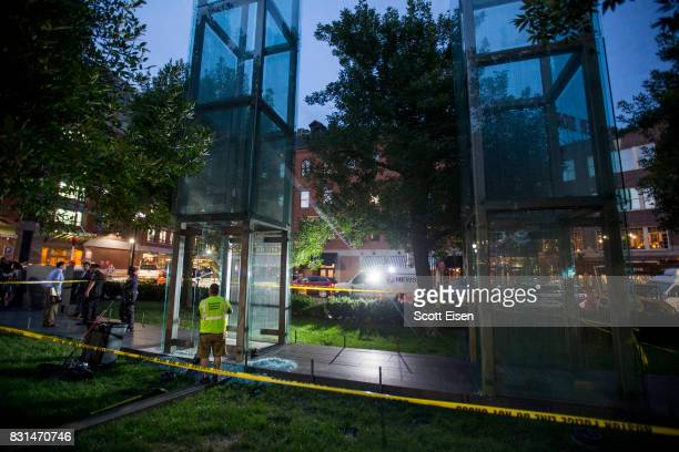 Workers clean up broken glass at the New England Holocaust Memorial that was vandalized when a rock was thrown through a panel that was part of it on...