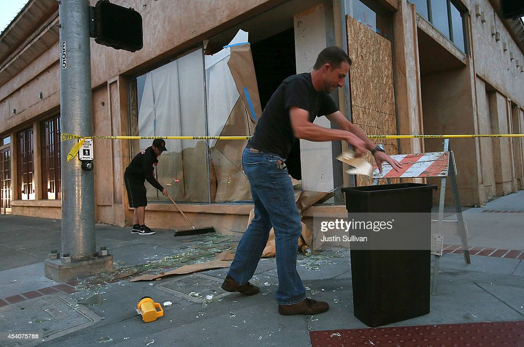Workers clean up broken glass in front of a destroyed buillding following a reported 6.0 earthquake on August 24, 2014 in Napa, California. A 6.0 earthquake rocked the San Francisco Bay Area shortly after 3:00 am on Sunday morning causing damage to buildings and sending at least 70 people to a hospital with non-life threatening injuries.