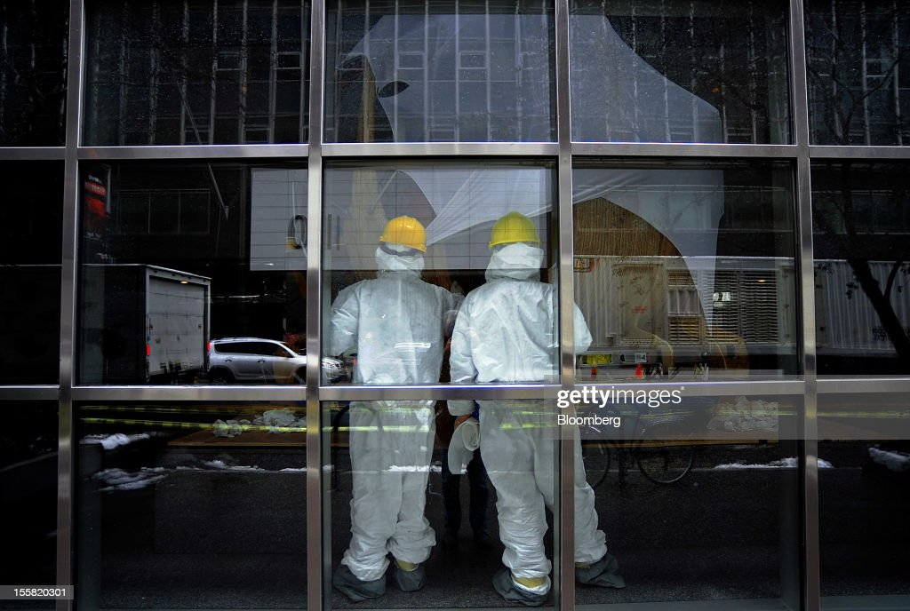 Workers clean up damage at a building in the lower Manhattan area of New York, U.S., on Thursday, Nov. 8, 2012. New York-area residents shoveled several inches of snow and airlines prepared to resume flights as the region coped with a nor'easter that slowed the recovery from superstorm Sandy. Photographer: Peter Foley/Bloomberg via Getty Images