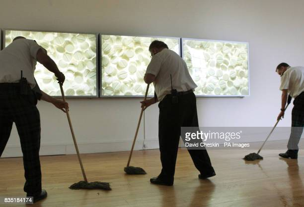 Workers clean up in the Damien Hurst room before a press view of the Artist Rooms featuring the works of Warhol Woodman Celmins and Gallagher at the...