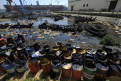 Workers clean up oil from the water at a dock in the port city of Dalian in China's northeastern Liaoning province on July 27 2010 China said an oil...