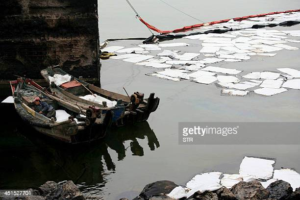 Workers clean up the oil slick with special paper on the river of Jiaozhou Bay after an oil pipeline exploded ripping roads apart turning cars over...