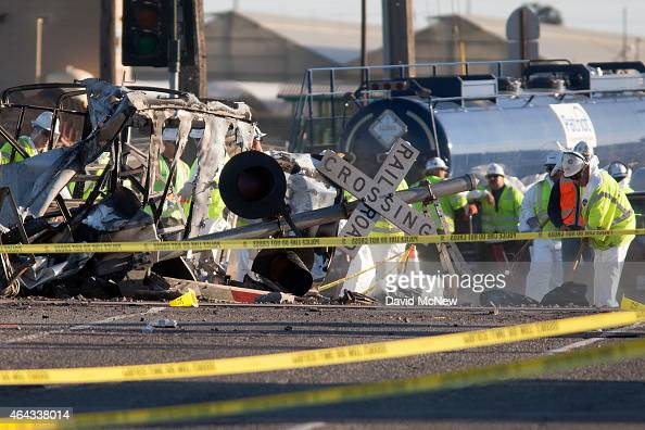 Workers clean up the street near the burned remains of a truck and trailer at the site where a Los Angelesbound Metrolink train derailed in a fiery...