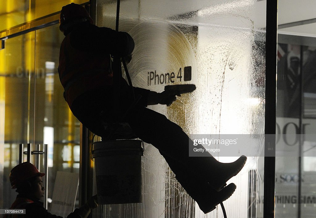 Workers clean up traces of eggs from the windows of Sanlitun Apple store on January 13, 2012 in Beijing, China. Apple customers who waited overnight for the launch of the new iPhone 4S turned angry and pelted the flagship store with eggs after it failed to open due to the large crowds.