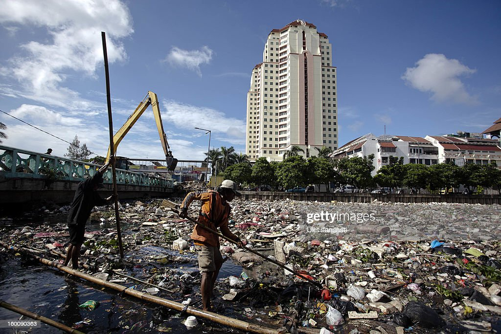 Workers clean up waste that was piled up by the flood at Pakin river in North Jakarta on January 26, 2013 in Jakarta, Indonesia. With heavy rain forecast for January 26-28, Indonesian authorities have organised the use of generators and cloud-seeding measures to defuse rain-laden clouds to help prevent further flooding of Jakarta, following last week's floods which claimed the lives of 32 people.