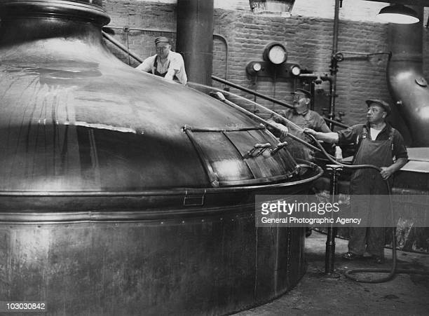 Workers cleaning one of the vats at a brewery in Germany circa 1930