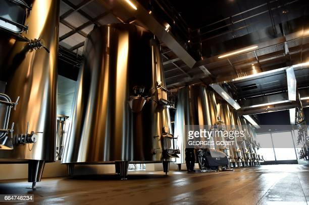 A workers cleans the floor by the vats in the wine cellar of the Chateau Pedesclaux in Pauillac on March 31 2017 Famous architects transform the...