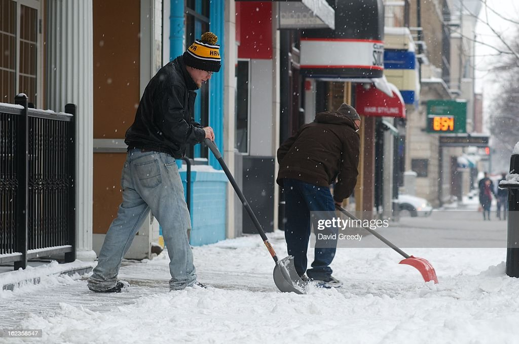 Workers clear a sidewalk after a winter storm left more than six inches of snow on February 22, 2013 in Iowa City, Iowa. The winter blizzard continues to move across the entire midwest, dumping up to a foot of snow in places as it moves east.