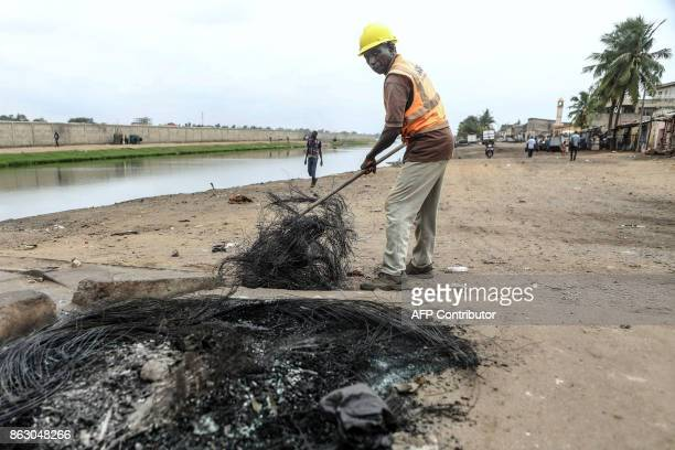 Workers clear a street following an antigovernment protest in Lome on October 19 2017 Protesters erected makeshift barricades and blocked roads in...