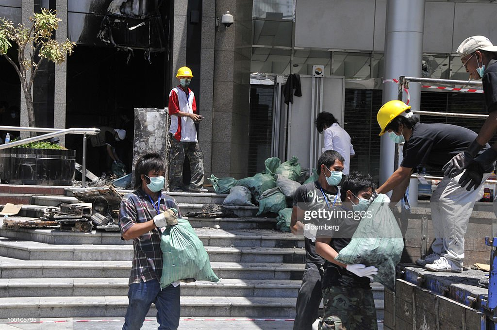 Workers clear debris and burnt computers from the Stock Exchange of Thailand (SET) building after unrest in Bangkok, Thailand, on Friday, May 21, 2010. Thailand's stock exchange can open for trading at a backup site even though the main building was damaged in a fire during unrest, President Patareeya Benjapolchai said today. Photographer: Udo Weitz/Bloomberg via Getty Images