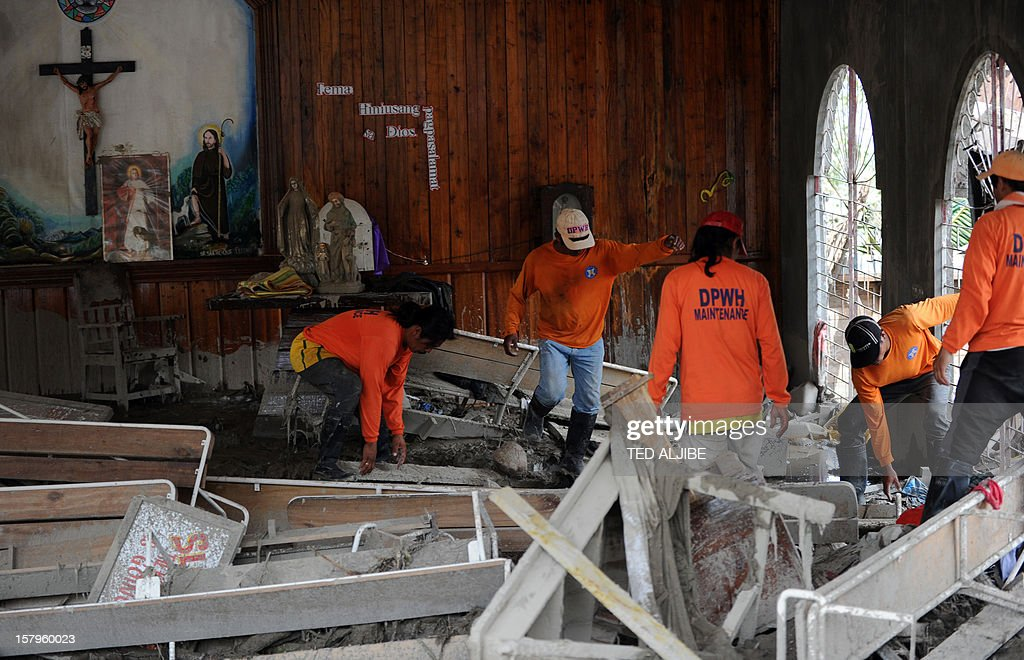 Workers clear debris inside a church swept in by flash floods caused by Typhoon Bopha in the village of Andap in the town of New Bataan in Compostela Valley province on December 8, 2012. Hungry and homeless typhoon survivors appealed for help on December 8 as the ravaged southern Philippines mourned its more than 500 dead and desperate people in one hard-hit town looted shops in search of food. AFP PHOTO / TED ALJIBE