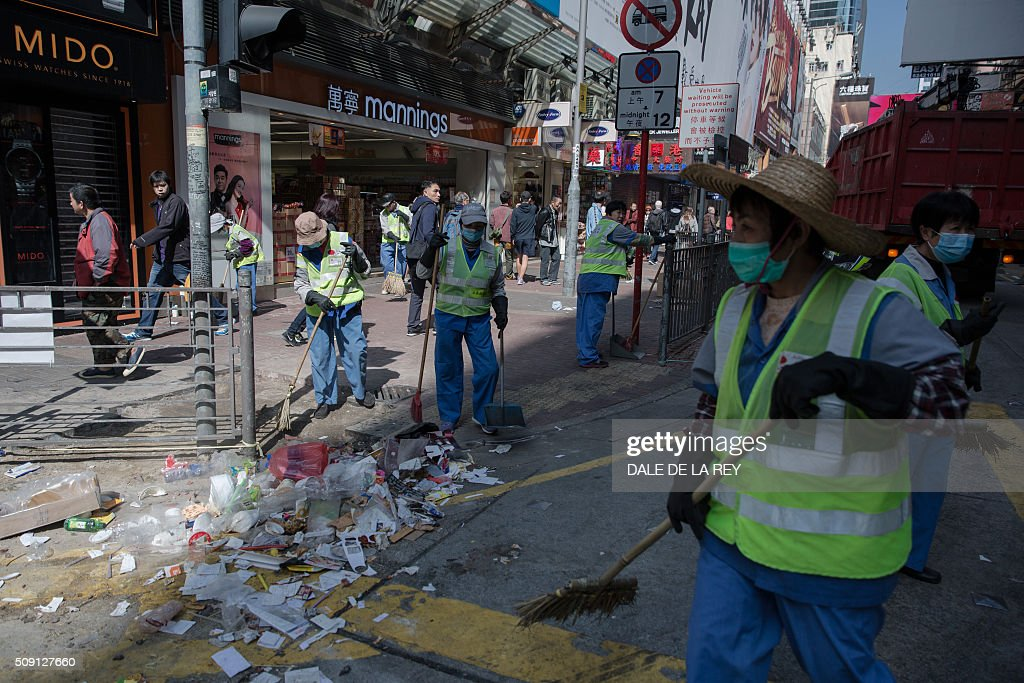 Workers clear debris on a street following overnight clashes between protesters and police in the Mongkok area of Hong Kong on February 9, 2016. Baton-wielding Hong Kong riot police fired warning shots and tear gas early on February 9 after a riot erupted in the busy district of Mongkok when officials tried to shift illegal hawkers, local radio reported. AFP PHOTO / DALE DE LA REY / AFP / DALE de la REY