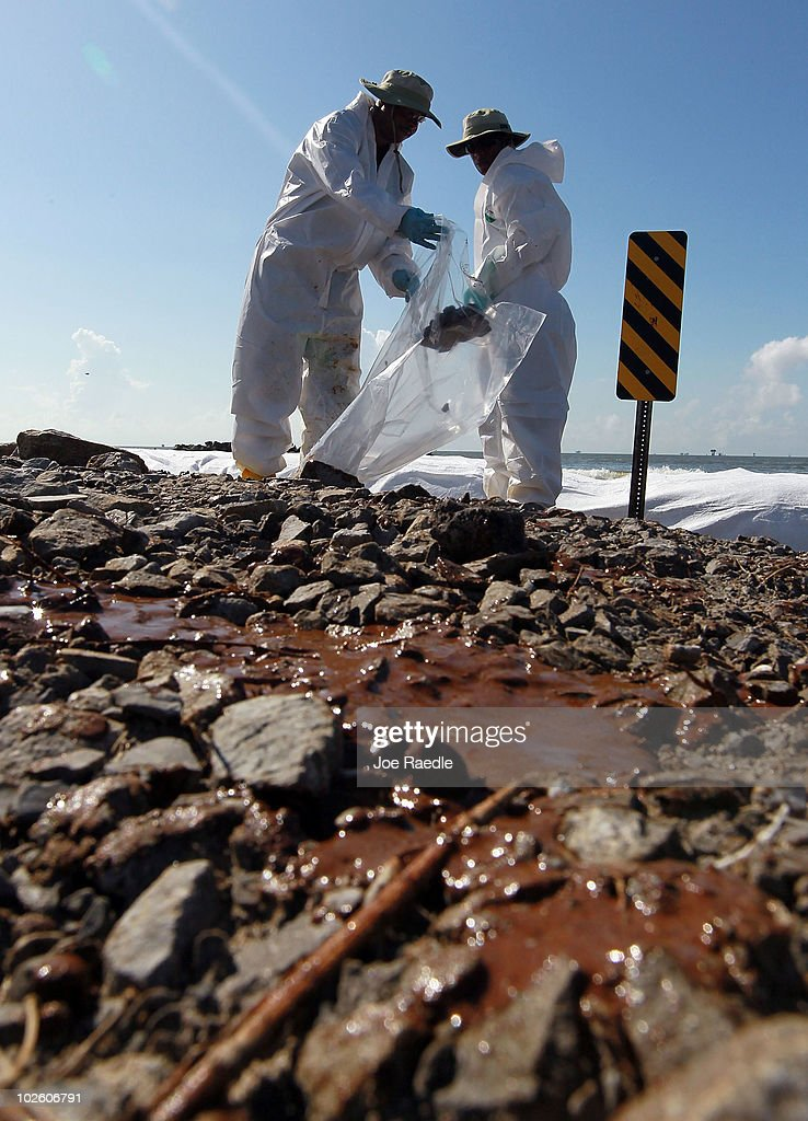 Workers clear off some of the oil washing on to Fourchon Beach from the Deepwater Horizon oil spill in the Gulf of Mexico on July 3, 2010 in Port Fourchon, Louisiana. Millions of gallons of oil have spilled into the Gulf since the April 20 explosion on the drilling platform.