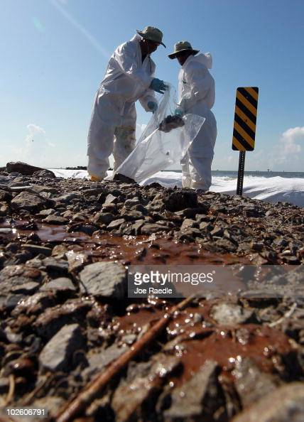 Workers clear off some of the oil washing on to Fourchon Beach from the Deepwater Horizon oil spill in the Gulf of Mexico on July 3 2010 in Port...