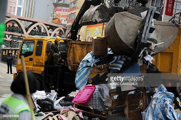 Workers clear rubbish and debris from the prodemocracy protest site in the Causeway Bay district of Hong Kong on December 15 2014 Police arrested...