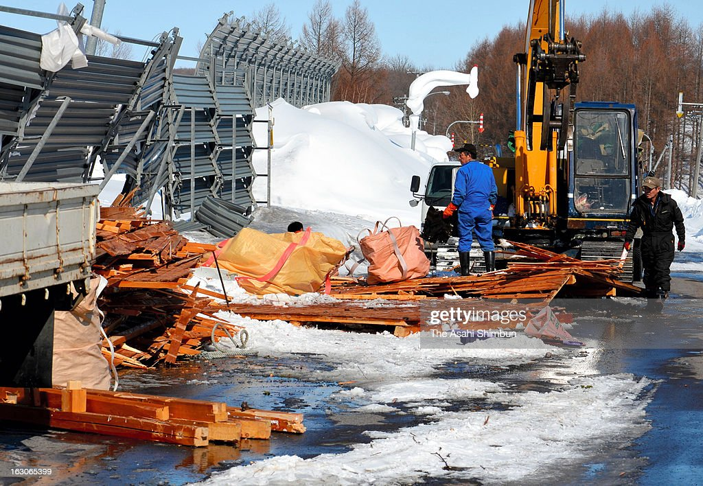 Workers clear the debris and broken snow fence a day after the blizzard hit Hokkaido, on March 4, 2013 in Abashiri, Hokkaido, Japan. The death toll rises to nine after a 76-year-old woman found frozen dead.