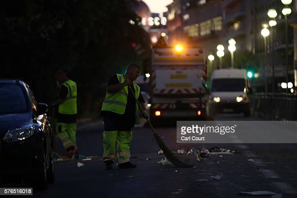 Workers clear the road along the Promenade des Anglais on July 15 2016 in Nice France A FrenchTunisian attacker killed 84 people as he drove a lorry...