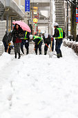 Workers clear the snow on the street near the JR Tachikawa Station on January 18 2016 in Tachikawa Tokyo Japan A lowpressure system brought heavy...