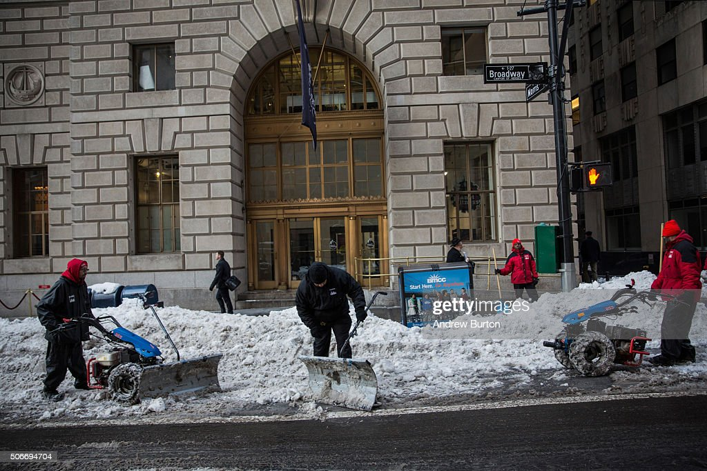 Workers clear the street of snow two days after a massive snow storm covered the east coast of the United States in snow on January 25 2016 in New...