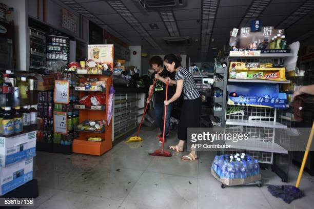 Workers clear water and damaged goods from a convenience store in Macau on August 24 2017 The death toll from Severe Typhoon Hato rose to at least 16...