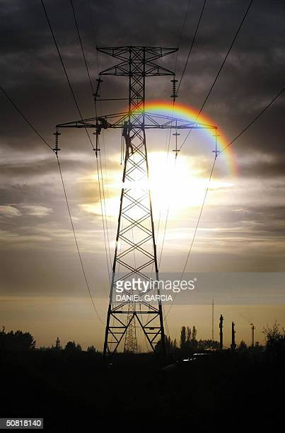 ENERGY Workers climb an energy tower to remove a glass insulator to replace it for an organic one 21 October 2003 on the outskirts of Mendoza...