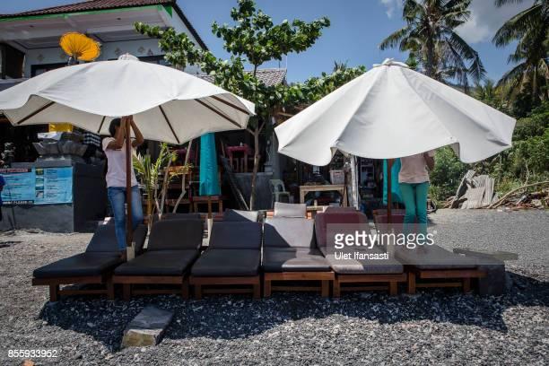 KARANGASEM BALI INDONESIA SEPTEMBER 30 Workers close the beach umbrellas at Amed beach as emptied of tourists on September 30 2017 in Karangasem...