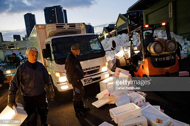 Workers collect boxes used to store fish and other seafood goods in packed ice at the Tsukiji fish market on February 28 2012 in Tokyo Japan Handling...