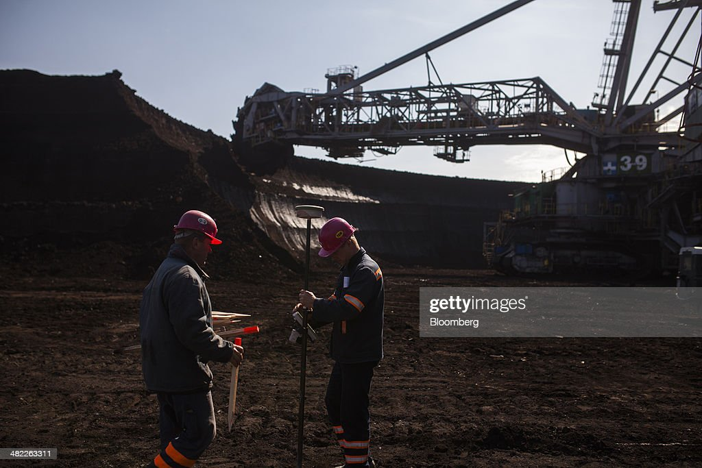 Workers collect measurement data on excavated earth on the pit floor near a giant excavator during lignite, also known as brown coal, digging operations at the open pit mine operated by PGE Elektrownia Belchatow SA near Belchatow, Poland, on Wednesday, April 2, 2014. Polish power prices are set to stay above German contracts through 2015, reversing a historic discount, as the cost of keeping plants open in the eastern European nation is factored in, according to Vattenfall AB. Photographer: Bartek Sadowski/Bloomberg via Getty Images