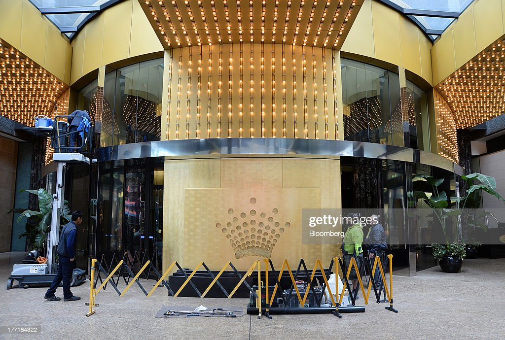 Workers conduct maintenance work near the Crown Ltd. logo displayed outside the Crown Towers hotel, part of the Crown Melbourne casino and entertainment complex, in Melbourne, Australia, on Wednesday, Aug. 21, 2013. Crown Ltd., the gaming company controlled by billionaire James Packer, is scheduled to announce full-year results on Aug. 23. Photographer: Carla Gottgens/Bloomberg via Getty Images