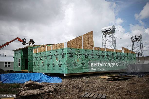 Workers construct a new 'Make it Right Foundation' home along the rebuilt Industrial Canal levee wall in the Lower Ninth Ward on May 18 2015 in New...