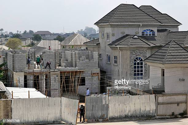 Workers construct a new residential building in Port Harcourt Nigeria on Tuesday January 2016 Twenty years after the oilpollution crisis in the Niger...