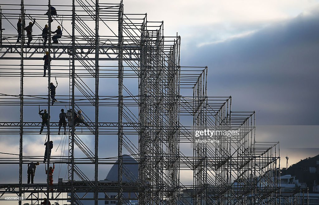 Workers construct the FIFA Fan Fest stage (L), where fans will be able to watch games broadcast live, on Copacabana Beach on June 4, 2014 in Rio de Janeiro, Brazil. Brazil has won five World Cups, more than any other nation. The 2014 FIFA World Cup kicks off June 12 in Brazil.