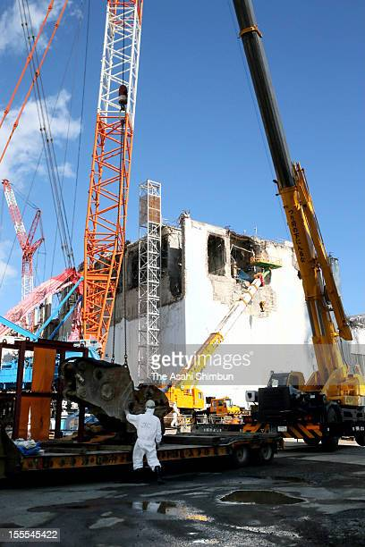 Workers continue decommissioning work at the fourth reactor building of the Fukushima Daiichi Nuclear Power Plant during the press tour on October 12...
