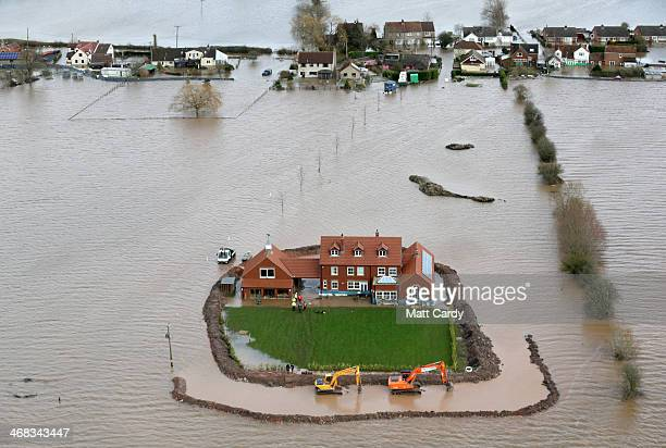 Worker's continue to build flood defences around Moorland resident Sam Notaro's house in the flooded village of Moorland near Bridgwater on the...