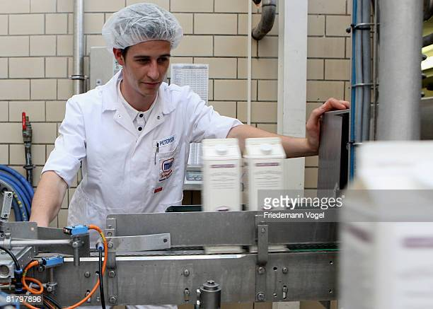 Workers control filled milk cartons speed along a conveyor belt at the MeyereiTrittau dairy plant on July 2 2008 in Trittau Germany German dairy...