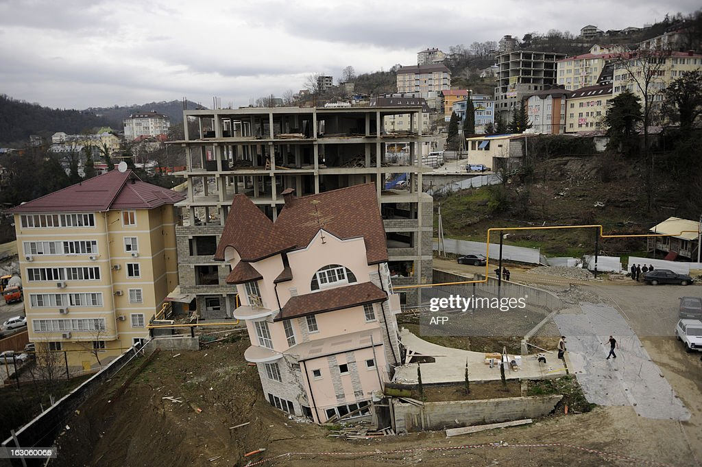 Workers cordon off a leaning building in the Russian Black Sea resort of Sochi, on March 4, 2013 . A three-storey apartment building under construction leaned yesterday in Sochi after a vehicular road traffic tunnel being constructed for the 2014 Winter Olympics had collapsed nearby, the local media said. There were no casualties reported.