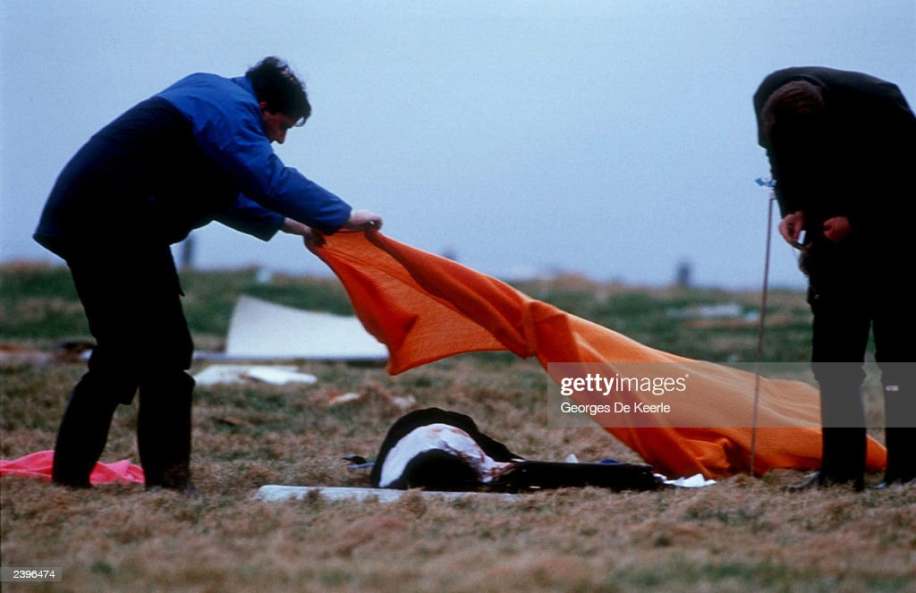 Workers cover the body of a victim of Pan Am flight 103 December 23, 1988 in Lockerbie, Scotland. All 270 passengers and crewmembers on the plane were killed. Two Libyans accused of blowing up Pan Am flight 103, Abdel Basset al-Megrahi and Al-Amin Khalifa Fahima, pleaded not guilty February 2, 2000. U.N. diplomats said August 12, 2003 that the U.S., Britain and Libya have reached an agreement that Muammar al Gadhafi's government would renounce terrorism, provide compensation to the families of the Pan Am victims and accept responsibility for the 1988 mid-air bombing of the plane over Lockerbie, Scotland, which killed more than 270. The $2.7 billion settlement that Libya is expected to pay is about $10 million per victim and will be placed into the U.N-controlled Bank for International Settlements in Switzerland. The three governments met August 11, 2003 in London to discuss how Libya could meet the final requirements needed for the removal of U.N. sanctions imposed after the bombing.