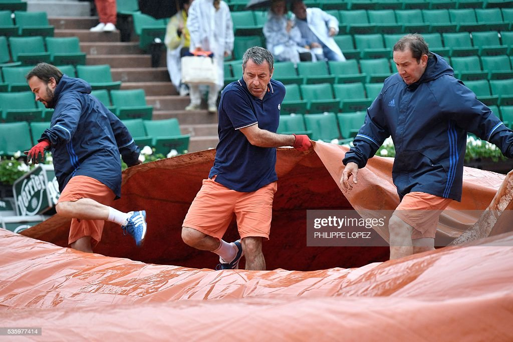 Workers cover the court as play is interrupted due to rain at the Roland Garros 2016 French Tennis Open in Paris on May 31, 2016. / AFP / PHILIPPE